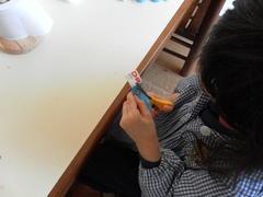 As crianças cortaram tiras de embalagens tetrapack para fazerem rolinhos.
