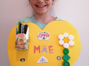 Produto final, quadro com porta lápis para a mãe, apresentado pela autora. É visível o selo da Tetra Pak, o símbolo FSC e que as embalagens utilizadas são da marca Compal.