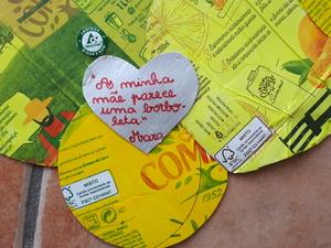 As crianças recortaram corações pequenos com as embalagens de sumo e escreveram mensagens sobre as mães.