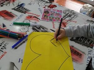 Criança a desenhar num coração amarelo.