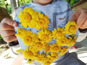 Coração feito com uma embalagem de leite e decorado com flores silvestres.