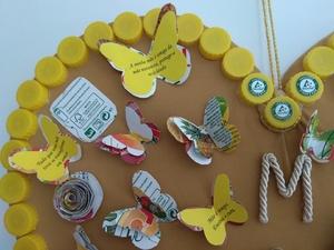 foto 2 identifica os símbolos exigidos e a forma como foram utilizadas as embalagens para decorar o coração com flores e borboletas. E ainda a aplicação das frases.