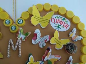 foto 3 identifica os símbolos exigidos e a forma como foram utilizadas as embalagens para decorar o coração com flores e borboletas. E ainda a aplicação das frases e as tampinhas amarelas que contornam o coração.