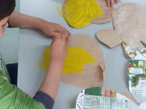Fase de confeção - pintura em amarelo da face interior das embalagens.