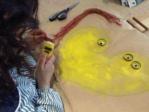 Materiais de desperdício para dar vida ao usado. Com cordas que pintamos de laranja, amarelo e vermelho, fizemos os cabelos da mãe e da filha. Com caricas, fizemos os olhos.