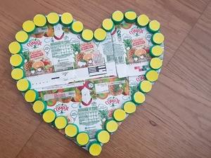Fase de Construção II. 1º - Recortar o coração desenhado na folha de papel; 2º - Colar o coração recortado ao cartão para forrar o fundo; 3º - Recortar o cartão de modo a ficar o coração recortado de papel; 4º - Colar as embalagens cartonadas Tetra Pa