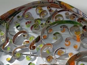 Imagem de pormenor em que é possível ver, de modo ampliado, as espirais feitas a partir de embalagens de Compal.