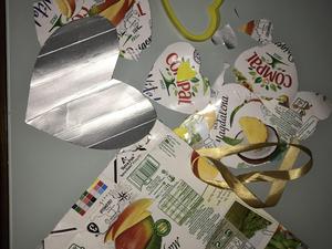 Em construção... As embalagens Tetra Pak da Compal foram cortadas, em forma de coração, de diversos tamanhos. Um coração grande servirá de base para colar os restantes corações com cola quente. Atrás será colada uma fita de cetim já usada.
