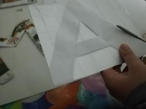 Recortando as letras da palavra MÃE, nos restos das embalagens Tetra Pak da compal.