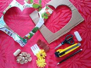 Preparação dos materiais para a construção do coração.  Ilustra materiais utilizados na elaboração do coração, nomeadamente cartão aproveitado de uma caixa; embalagem Tetra Pak da Compal; rolhas de cortiça, bem como os moldes para o coração e as flores.