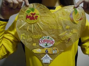 A autora do trabalho com uma camisola amarela onde se destaca o coração elaborado