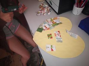 Colagem dos pedaços (quadrados/retângulos) de embalagens da Compal no coração amarelo também com cola quente, aplicando a técnica do mosaico.