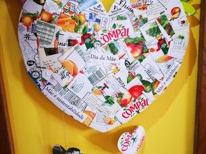 Plano de pormenor de um dos lados do coração, onde é visível a marca Compal, os símbolos Tetra Pak, o símbolo FSC, bem como as frases alusivas ao Dia da Mãe.